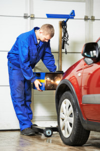 auto mechanic at car headlight checkup